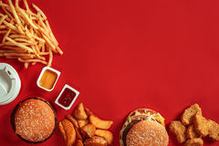 Burger and Chips. Hamburger and french fries in red paper box. Fast food on red background. Royalty Free Stock Photography