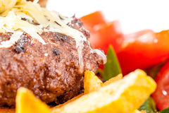 Burger with Chips and Tomato. Closeup of beef burger with chips and tomatos in the background. Cheese melted over top Royalty Free Stock Photos