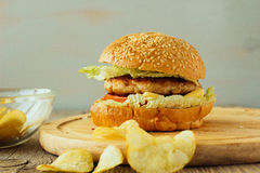 Burger and chips on wooden plate horizontal Royalty Free Stock Photos