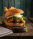 Burger with chopped meat, egg and arugula on a wooden table Stock Photos