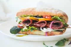 Burger ciabatta με το καπνισμένο λουκάνικο, το φρέσκο μίγμα σαλάτας, τις ντομάτες, τη σάλτσα pesto και τα κρεμμύδια Στοκ φωτογραφία με δικαίωμα ελεύθερης χρήσης