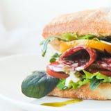 Burger ciabatta mit geräucherter Wurst, neuer Salatmischung, Tomaten, Pestosoße und Zwiebeln Stockfotografie