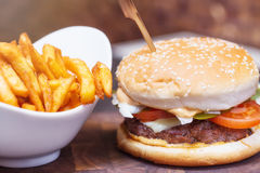 Burger close up with fresh tomato, cheese, meat and french fries Royalty Free Stock Images