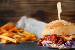 Burger with coleslaw and cheese on wood and fries. authentic homemade burger with royalty free stock photo