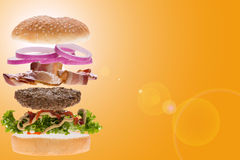 Burger concept for menu. Soaring hamburger components with yellow background for menu Stock Photo