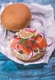 Salmon burger on blue. Burger with cream cheese, smoked salmon, red onion, capers and lemon on rustic blue table Stock Image