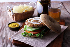 Burger with cucumber and  tomato. On  french fries background Stock Photography