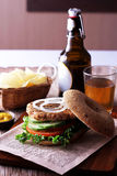 Burger with cucumber and  tomato. On  french  fries background Stock Image