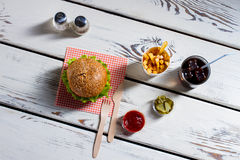 Burger, cutlery and pickle slices. Royalty Free Stock Images