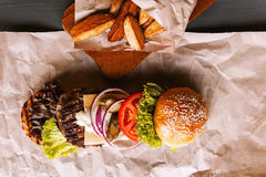 Burger decomposed into its components. On kraft paper on a wooden table. package of Chips Royalty Free Stock Photography
