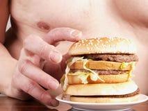 Burger in der Hand des Mannes Lizenzfreie Stockfotografie