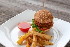 Burger des strengen Vegetariers, Bestandteile: Brötchen des indischen Sesams, Patty von Kichererbsen, Paprika stockfotos