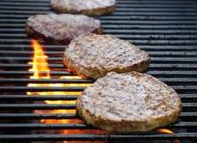 Burger, die über Flammen auf dem Grill kochen Lizenzfreies Stockfoto