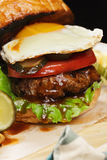 Burger with egg on a wooden board closeup Royalty Free Stock Photos