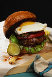 Burger with egg on a wooden board Stock Photography