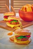 Burger fast food made at home, with meat, lettuce, tomato, cheese, pickles and mayonese on wooden board and table. Copy space. stock image