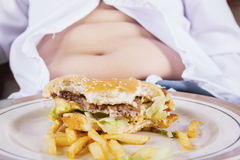Burger with fat belly. Close up of a half hamburger on the plate with fat belly of a boy Royalty Free Stock Image
