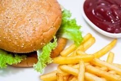 Burger with fat french fries and dressing Stock Images