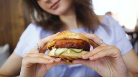 Burger in female hands close up leaking stock footage