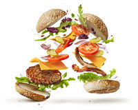 Burger with flying ingredients. Two burgers with flying ingredients isolated on white background royalty free stock photo