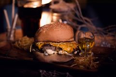 Burger food photo. Street food. Fresh tasty grilled beef hamburger cooked at barbecue on wooden table. Big cheeseburger Royalty Free Stock Photos