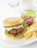 Burger with french fries. Delicious juicy burger with tomato, onion, pickles,lettuce and fries Stock Photography