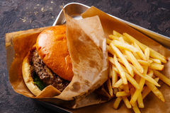 Burger and French fries in aluminum tray. Burger with meat and French fries in aluminum tray on dark background stock image