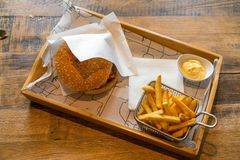 Burger, french fries, cheese sauce on a wooden base.  stock photography