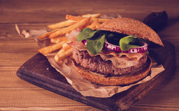 Burger and french fries close up on vintage style. Royalty Free Stock Photos