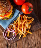 Burger and french fries close up on wooden background. Royalty Free Stock Image