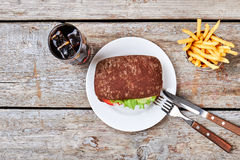 Burger, french fries and coke. Cutlery and food on plate. Time for lunch Stock Photos