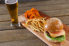 Burger and french fries with glass of beer Stock Photos