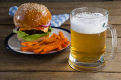 Burger and french fries in plate with glass of beer. On wooden table Royalty Free Stock Photography