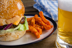 Burger and french fries in plate with glass of beer Stock Photography