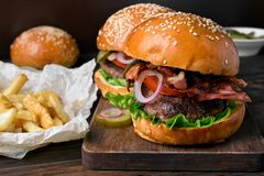 Burger and french fries. On wooden table Royalty Free Stock Photography