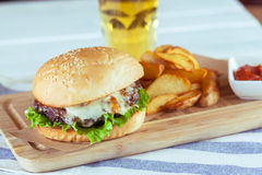 Burger and french fries. On wooden table royalty free stock images
