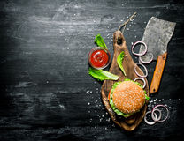 The Burger and the fresh ingredients. On the old Board. On a black chalkboard.  Top view Royalty Free Stock Photography