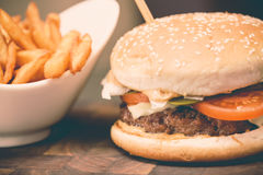 Burger with fresh tomato, cheese, meat and french fries. Selective focus Stock Photo