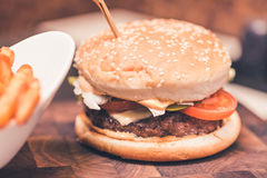 Burger with fresh tomato, cheese, meat and french fries. Selective focus Royalty Free Stock Image