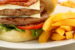 Burger And fries. Double decker hamburger with bacon and cheese and golden fries Stock Photos