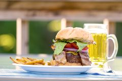 Burger, fries and beer on the deck. Big Bacon Cheeseburger with lettuce, red onion and tomato on a sesame seed bun. Resting on a plate outdoors, with a beer stock photo