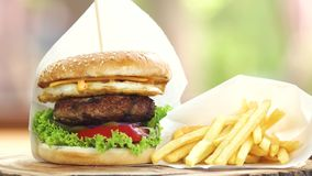 Burger and fries on board. Delicious fast food stock footage