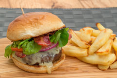 Burger and fries with a brioche bun. Cheeseburger and fries with a brioche bun - studio shot with a shallow depth of field stock photos