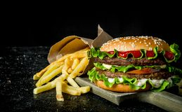 Burger with fries on the cutting Board. On black rustic background royalty free stock images