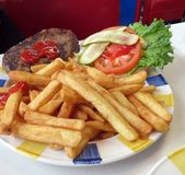 Burger and Fries. A hamburger with the works, along with a side order of French fries at the diner royalty free stock photo