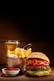Burger with fries and pint of lager. Freshly made beef burger with basket of fries, bowl of ketchup and pint of lager on wooden table, vertical images with copy Royalty Free Stock Image