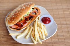 Burger with fries and tomato ketchup. On bamboo mat Stock Photo