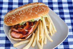 Burger with fries and tomato ketchup. On a blue checkered tablecloth Royalty Free Stock Image