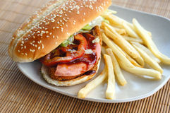 Burger with fries and tomato ketchup. Burger with fries on bamboo mat Royalty Free Stock Photos