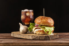 Burger with garlic and cola on wooden cutting board with copyspace. Homemade burger with beef patty, lettuce, tomato, cheese and red onion served with garlic Stock Image